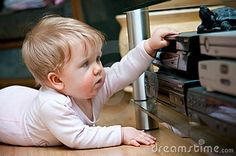 Baby girl crawling on the floor, messing with home audio video equipment.