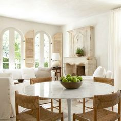 Breathtaking French Country living room with arched French doors, rustic shutters, antique French limestone fireplace, white furniture, and dining area with Saarinen table and rush woven chairs. Design by Pamela Pierce.