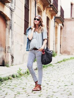 Mireia Oller of My Daily Style in a t-shirt, striped pants, and gladiator sandals