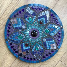 A beautiful mandala mosaic panel.  This is an original, one-of-a-kind piece of art.  I used a mixture of purple, blue and teal tiles in both a matte and gloss finish. Ceramic copper speckled dots accentuate the petals, and a mix of moonshine glass tiles add that finishing sparkle!  The base is made from MDF and hand painted on the back and sides to finish.  Diameter: 30cm (12in) Depth: 1cm This item is intended for indoor use only. It would look lovely hung on a wall or displayed on a stand…