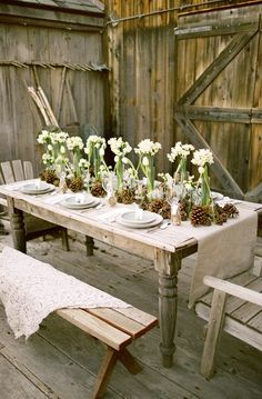 Rustic with burlap, pinecones and simple glass vases with a few flowers