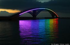 The Xiying Rainbow Bridge. The Xiying Rainbow Bridge is an elevated pedestrian walkway located in Magong, Penghu County in Taiwan. The bridge is lined with a thin neon band that reflects a rainbow onto the water's surface below at night. Mundo Design, Image New, Pedestrian Bridge, Chef D Oeuvre, Le Chef, Light Installation, Rainbow Bridge, Over The Rainbow, Rainbow Light