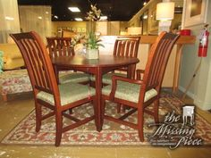 """Drexel dining table in a dark finish with four slat back chairs. The chairs have a green upholstered seat. Measures 46""""round; (1)24""""leaf. Nice size for a kitchen area or smaller dining room."""