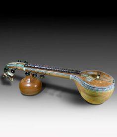 VINA DE SARASWATI Se podría afirmar que la Vina de Saraswati es el instrumento por excelencia de la Música Carnática, la tradición musical del Sur de la India. Junto con el Bansuri, la Vina está asociada a la diosa de la música, Saraswati.  Es uno de los pocos cordófonos indios que presentan trastes fijos. En este caso son veinticuatro trastes de cobre, y van montados sobre una amalgama de cera de abeja con adhesivos vegetales. Se fabrica en madera de yaca y, además de la caja de resonancia…