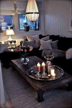 black couches softened with pillows; love the coffee table