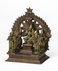 At the front is Hanuman, the monkey deity devoted to Rama. and a figure holding two fly-whisks (chauri), probably Rama's half-brother Shatrughna. At the back, standing with a bow over his shoulder and his palm together in the anjali mudra worship gesture is the recognisable figure of Rama's closest brother, Lakshmana.