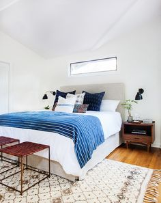 Bright, white bedroom with pretty Moroccan rug, indigo throw over white linens, lots of pretty textiles.