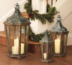 Green garland, pine cones on stair railing with lanterns for christmas holiday decor Pottery Barn Lanterns, Lanterns Decor, Candle Lanterns, Large Lanterns, Rustic Lanterns, All Things Christmas, Christmas Holidays, Merry Christmas, Happy Holidays