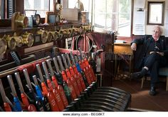 An old railway signal box with levers, clocks and signalman at Sheffield Park station on the Bluebell Railway