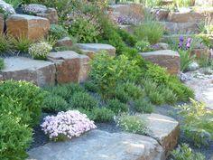 Mit Natursteinblöcken abgefangene Böschung: mediterraner Garten von Gärten für Auge und Seele
