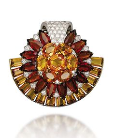 [IMAGE 2} RETRO CITRINE AND DIAMOND JEWELLERY, BY CARTIER Comprising a clip brooch of sunflower design, set with vari-cut two-toned citrines, enhanced by circular-cut diamond detail and a pavé-set diamond scrolling top, to the rectangular-cut citrine crescent trim, a pair of ear pendants en suite, mounted in platinum and gold, 1950s, brooch 5.3 cm, earrings 4.5 cm Signed Cartier London.
