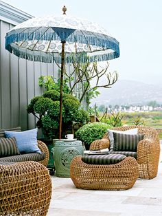 To accessorize this Southern California patio, cheeky island finds, such as an umbrella, relax the space. With its batik-style print and fringe trim, it sets a laid-back tone for the outdoor space. The furniture offers a twist on classic woven pieces, and its lightweight nature makes it great for rearranging. (Photo: David Tsay)