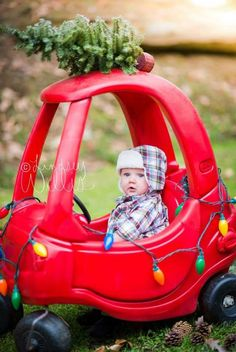 Merry Christmas - baby in red toy car with Christmas lights