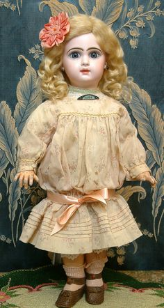 "Lovely French ""Bebe"" antique doll with paperweight eyes and what appears to be vintage clothing."