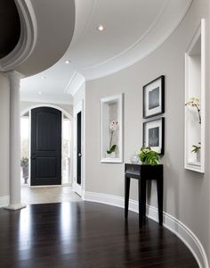 A light grey entrance hall is grand and inviting. The tone is perfect for this space as it flows nicely against the curved wall, finished with a dark wooden floor (by Jane Lockhart Interior Design).