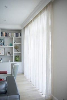 Heavy voile curtains hung on recessed wood pelmet