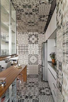 Impossível não notar o revestimento que cobre a cozinha do chão até o alto – literalmente. O material integrou os espaços e definiu uma decoração mais neutra