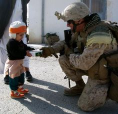 Marine Corps. Col. Michael Gann, the II Marine Expeditionary Force Forward operations officer for Afghan National Security Forces Development stationed at Camp Lejeune, N.C., hands a young girl a package of candy while in Zaranj, Nimroz province.(Photo by Spc. Chelsea Russell)