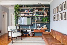 Sala de estar tem parede pintada de cinza com prateleiras instaladas com cremalherias e sofá vintage.