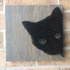 String art image of a black cat peeking on a grey stained wood board. Nails reflecting the light create a beautiful sparkle. Stringing patten very symmetrical and organized. The cats eyes left unstrung to show the grey stain through. This piece measures 9 by 9 inches and has a sawtooth