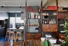 A estante vintage serve como divisória entre a sala e o corredor que leva aos quartos.