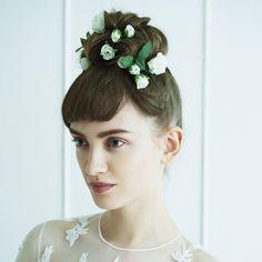 頭のてっぺんにざっくりと大きなシニョンを作り、白のプチローズをランダムに咲かせて。8:2で分けた短いバングスが、コケティッシュな印象をプラスして。造花のバラ/スタイリスト私物 ドレス¥1,000,000(レン...
