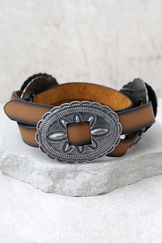 "Dance the night away with the Desert Sunset Silver and Brown Belt! This vegan leather skinny belt is accented with trendy, engraved silver conchos. Belt measures 36.5"" long with seven hole adjustments."