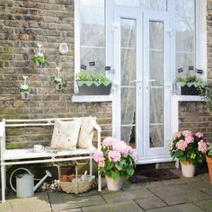 Love the shabby chic look. The white bench with the pillows, pink flowers in the pots, watering can and basket under the bench ~ lovely!! ~ Wish my bricks had that same lovely look...