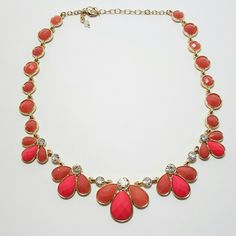 Coral-colored Bib Necklace Gold-tone metal surrounds coral-colored faux stones. This necklace is perfectly on trend and in excellent condition. There are no missing stones and the clasp is in good working order. Jewelry Necklaces
