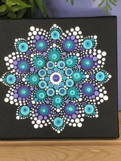 Hand painted dot mandala on a 5x5 stretched canvas. Painted with acrylic paints.