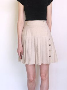 Beautiful vintage skirt made of beige- gray wool blend. Upper part is fitted, bottom flared, pleated and decorated with row of horn buttons.