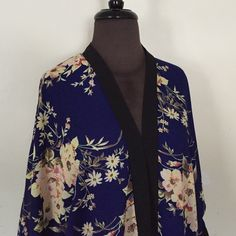 """Blue Floral Kimono Dark blue kimono with a pretty floral pattern and black trim. Slight hi-lo hem. Worn once, in perfect condition. Size large, will fit up to a 1X. Measures roughly 27"""" across when flat, 26"""" long in the front. NO TRADES. PRICE IS FIRM. Charlotte Russe Tops"""