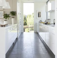 Sleek galley: One would hardly notice this kitchen is narrow due to the glossy white cabinets and white walls.