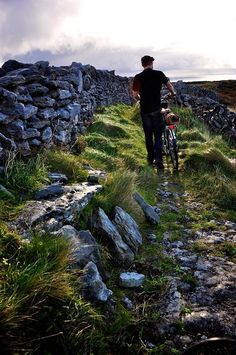 Walking a bicycle along the cow paths of Inishmore, Aran Islands, Ireland.