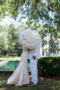 bride and groom kiss under a parasol