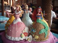 """Disney Princess Doll Cakes - I made 5 disney princess doll cakes for my granddaughter's 5th birthday. What a challenge. I purchased dolls from the store instead of using the traditional doll cakes with no torso. Consequently I had to add 4"""" of cake under each doll cake skirt to make them high enough -- I baked 15 cakes total! But a HUGE hit with my granddaughter and everyone (even strangers) at the pizza place."""