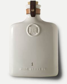 """The Ceramic Flask is a newly designed drinking flask made with quarter inch ceramic white slip cast and accented with 2 leather straps, brass stud and brass button. 4.25 x 6.5"""" Oil tanned and vegetabl"""