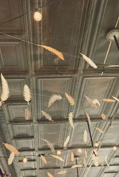 paper feathers strung amongst bistro lights Fun alternative to garland Diy Pompon, Feather Garland, Feather Decorations, Stall Decorations, Hanging Decorations, Feather Art, Feather Headband, Hanging Lights, Do It Yourself Baby