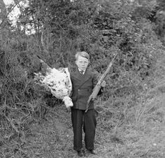 Original caption: France: He Lost His Friend. This small French boy is carrying flowers to the grave of his friend who was killed when he joined the Allies in the fight for France. The youth carries his friend's gun, which was blasted from his hand by a shell. Throughout France, the young people have rallied to arms to help in the liberation of their homeland.