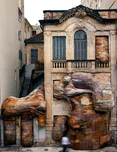 This sculpture created out of splintered and discarded plywood looks like it's consuming this building. By Henrique Oliveira