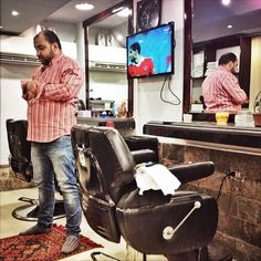 A hair dresser prays in his barber shop while an Ahly player appears on TV during the Egypt Derby between Ahly and Zamelek, in Cairo, July 21, 2015. Photo by Cui Xinyu @peteraced