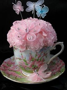Butterfly Love  This stunning pin cushion is a one of a kind and has been created by Andama Dujon for Extraordinary Things.  We have used a vintage Royal Albert English bone china duo/ teaset and we have matched the fabric roses perfectly to the wonderful vibrant pink pattern on the cup and saucer.  We have made this in cushion a little playful by adding two pink butterflys and then finished it off with three hand made butterfly hat pins.