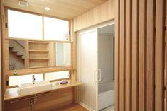 ユーティリティーや洗面脱衣室の壁や床、天井にヒノキやヒバを使用。洗面台はオリジナルの造作家具。