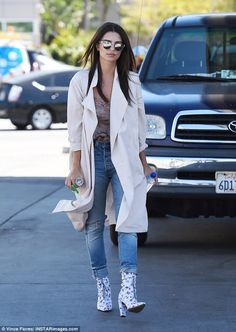 So chic:Emily Ratajkowski wore a pair of light denim jeans, white patterned boots and a long white trench coat as she walked around LA on Wednesday