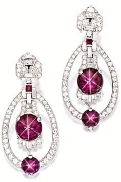Pair of star ruby and diamond earrings, Yard. Of Art Deco design, each suspending an oscillating cabochon star ruby altogether weighing approximately 6.89 carats, within a frame set with baguette and circular-cut diamonds, highlighted by a similar cabochon star ruby altogether weighing approximately 3.00 carats, to a surmount set with circular-cut, baguette and half moon-shaped diamonds, the diamonds altogether weighing approximately 1.80 carats, mounted in platinum, signed. Via Sotheby's.