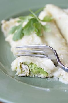 Cilantro Lime Chicken Enchiladas  Ingredients:        2 cups shredded chicken       2 avocados, diced       couple cilantro leaves, chopped       1/4 cup sour cream       1/4 cup lime juice       1 tsp ground cumin      Salt and pepper      12 flour tortillas       1 10 oz. can green chile enchilada sauce       1 – 1 1/2 cups shredded queso quesadilla or Mexican blend cheese