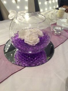 Fish bowl wedding centrepiece for purple themed weddings. Cadburys purple beads, Ivory roses and Ivory butterfly. Available to hire for your wedding in Swansea, Neath, port talbot, Bridgend, porthcawl, Llanelli, Carmarthen and surrounding areas of South Wales from affinity event decorators www.affinityeventdecorators.com