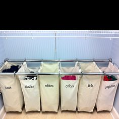 Embroidered canvas laundry bags hanging on chrome clothing rods.
