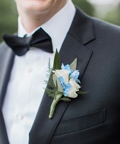A punch of color for the groom: accessorize his black tux with a boutonnière that is in sync with your wedding motif. Featuring white roses, blue accents and eucalyptus greenery. Boston Florist, Groomsmen Wedding Photos, Wedding Motifs, Copper Penny, Black Tux, Corsages, Boutonnieres, Blue Accents, White Roses