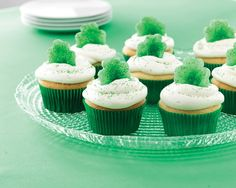 Prep for St. Patty's Day by making these festive cupcakes. First, bake and frost white cupcakes as you like. Then, flatten spearmint leaf candies with the Baker's Roller and use the shamrock-shaped Creative Cutter to create tasty cupcake toppers. Finish with a touch of green colored sugar or sprinkles. #PamperedChef